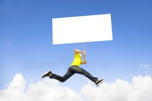 Man Holding A Billboard Jumping Into Blue Sky